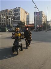 爱心接力:外卖小姐姐一手骑电动车,一手牵着盲人帮助过(红绿灯)马路。