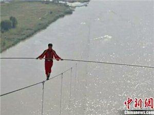 """""""高空王子""""阿迪力1日在黄河大峡谷成功通过一段1880米长,最高处距水面达180米的钢丝。"""