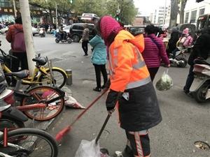 零下1度的郑州 环卫工路边手握扫帚睡着