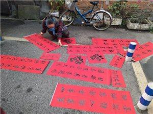 2月9日上午,九江书画院为社区居民义务写春联活动在九江路社区警务室举行