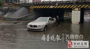 一轿车搁浅桥下水中,邹城交警雨中赤脚推车