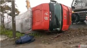 一辆半挂货车因雨天路滑发生侧翻!