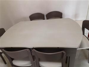 """折价出售全新""""得一""""牌餐桌椅一套,桌面可伸缩,面料耐高温、耐磨,原价六千五百元。有意者致电详谈。"""